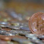 Bitcoin Münze neben Münzgeld